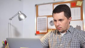 Young man office worker typing at notebook and thinking. Young serious man at work in the office. Office worker typing at notebook and thinking stock video footage