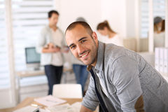 Young man at office working, colleagues in the back stock photography
