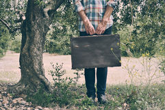 Young man with an old brown suitcase in a natural scenery Stock Image