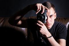 Young man with old camera. In dark studio Royalty Free Stock Photography