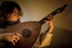 Young Man with Old Oud Guitar Lute. Young man with long blond hair sitting in dark environment and playing an Old Oud, Guitar Lute and looking at it. He is Royalty Free Stock Image