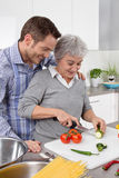 Young man and older woman cooking together in the kitchen. stock photos