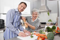 Young man and older woman cooking together in the kitchen. Stock Image