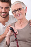 Young man and older woman. Young men helping an older woman Stock Image