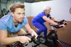 Young man and older woman working out in sport club royalty free stock photo