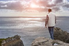 Free Young Man On Cliff`s Edge At Sunset Stock Photo - 101510890