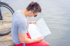 Young man, one happy tourist bicyclist with route map wearing in gray shirt with glasses Stock Photos
