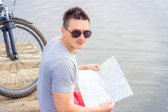 Young man, one happy tourist bicyclist with route map wearing in gray shirt with glasses Stock Image