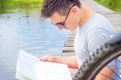 Young man, one happy tourist bicyclist with route map wearing in gray shirt with glasses Stock Images