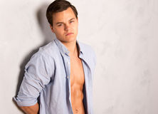 Young man in open shirt leaning against wall Royalty Free Stock Image