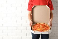 Young man with opened pizza box near white brick wall, space for text. Food delivery service royalty free stock photography