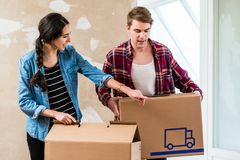 Young man opening a box while moving with his girlfriend into a new house. Young blond men opening a cardboard box while moving together with his girlfriend into Stock Photos