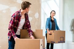 Young man opening a box while moving with his girlfriend into a. Young blond men opening a cardboard box while moving together with his girlfriend into a new Stock Images