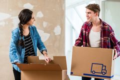 Young man opening a box while moving with his girlfriend into a. Young blond men opening a cardboard box while moving together with his girlfriend into a new Stock Photography