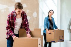 Young man opening a box while moving in with his girlfriend. Young blond men opening a cardboard box while moving together with his girlfriend into a new house Stock Image