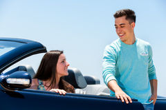 Young man opening car door to woman. stock image