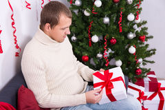 Young man opening christmas present box Royalty Free Stock Photos