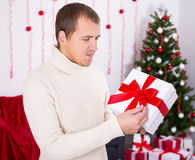 Young man opening christmas present box in decorated room Royalty Free Stock Image