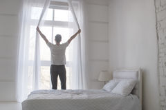 Young man opening curtains to welcomw morning and light, rear view, white Royalty Free Stock Photo