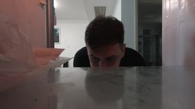 POV inside the refrigerator. A young man opening the fridge`s door and showing a disappointed face because it`s empty.