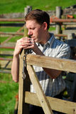 Young man opening a gate Stock Images