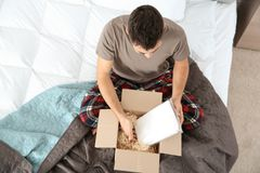 Young man opening parcel in bedroom stock photo
