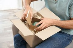 Young man opening parcel at home royalty free stock photo