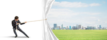 Free Young Man Opening White Curtain And Presenting Modern City Landscape Royalty Free Stock Photo - 89605575