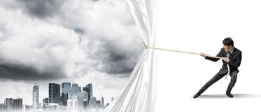 Young man opening white curtain and presenting modern city landscape Royalty Free Stock Photo