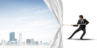 Young man opening white curtain and presenting modern city landscape Stock Photos