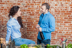 Young Man Opening a Wine Bottle with His Wife Stock Images