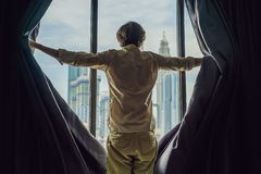 Young man opens the window curtains and looks at the skyscrapers in the big city stock image