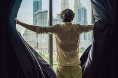 Young man opens the window curtains and looks at the skyscrapers in the big city royalty free stock photos
