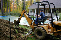 Young Man Operating Backhoe. Teen Male operating backhoe in a residential backyard project Stock Photos
