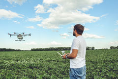 Young man operating of flying drone octocopter at the green field. Professional agriculture drone flying with blue sky Royalty Free Stock Image