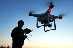 Young man operating of flying drone at sunset stock images