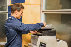 Young Man Operating Photocopier Machine. Young Handsome Man Operating High-Tech Photocopier Machine at the Office Royalty Free Stock Photos