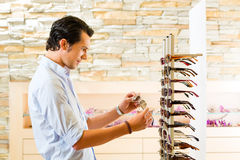 Young man at optician buying sun glasses Stock Image