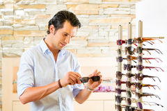 Young man at optician buying sun glasses Royalty Free Stock Image