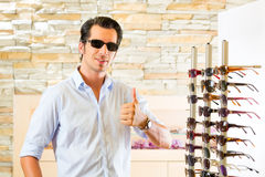 Young man at optician buying sun glasses Stock Images