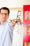 Young man at optician with glasses Royalty Free Stock Image