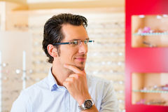 Young man at optician with glasses Stock Images