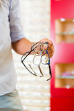 Young man at optician with glasses Royalty Free Stock Photos