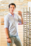 Young man at optician with glasses Royalty Free Stock Photo