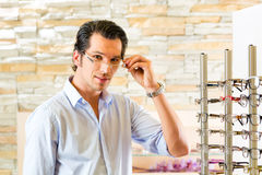 Young man at optician with glasses Stock Photos