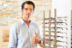 Young man at optician with glasses Stock Photo