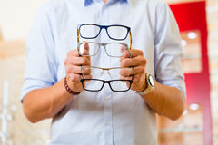 Young man at optician with glasses Royalty Free Stock Photography