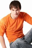Young man in orange. Portrait of young serious man in bright orange sweater on white background Royalty Free Stock Photography