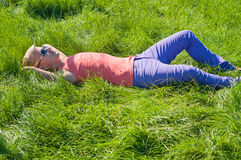 Young man in orange lying on the green grass Royalty Free Stock Photos
