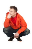 Young man in orange sweatshirt, full length Royalty Free Stock Image